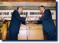 Photo of President Fujii presented the award certificates to Mr.Tuncoku